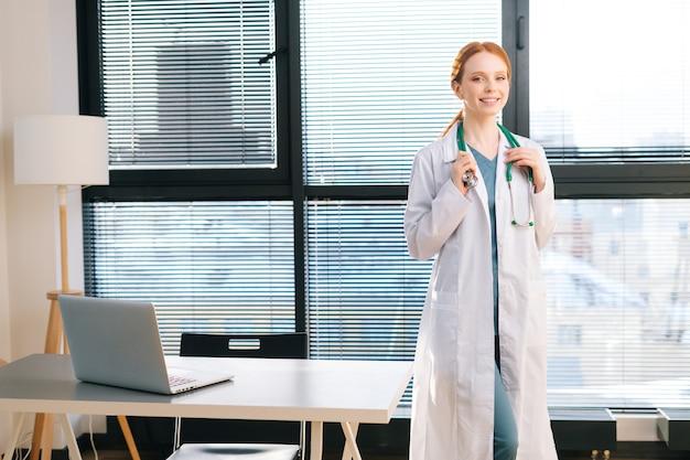Retrato de uma atraente médica em pé de jaleco branco no fundo da janela em um dia ensolarado no escritório da clínica médica.