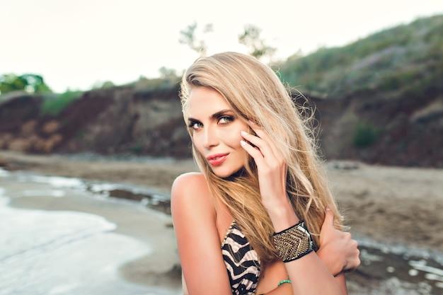 Retrato de uma atraente menina loira com cabelo comprido, posando na praia rochosa. ela está olhando para a câmera.