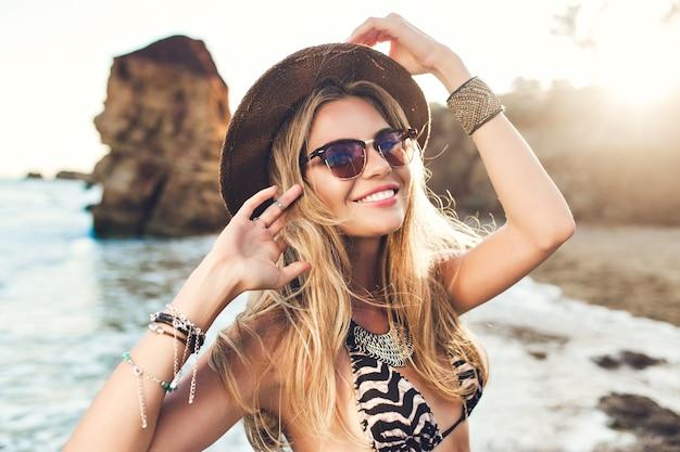 Retrato de uma atraente menina loira com cabelo comprido, posando na praia rochosa. ela está sorrindo.