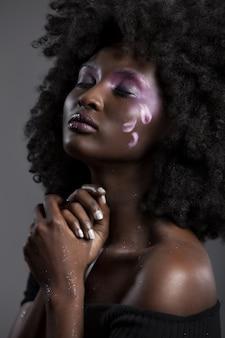Retrato de uma atraente mulher afro-americana com bela maquiagem, posando com os olhos fechados