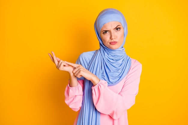 Retrato de uma atraente muslimah irritada descontente usando hijab, acusando o fingimento de contar isolado em um fundo de cor amarelo brilhante