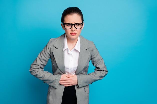 Retrato de uma atraente senhora de negócios doente, sentindo má digestão, diagnóstico, úlcera gastrite isolada sobre fundo de cor azul vibrante