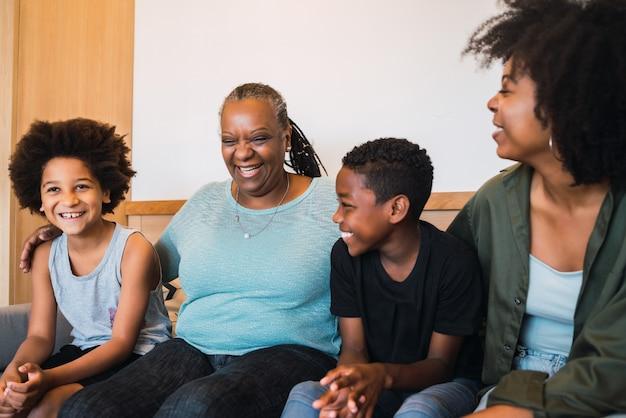 Retrato de uma avó afro-americana, mãe e filhos passando um bom tempo juntos em casa. conceito de família e estilo de vida.