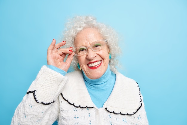 Retrato de uma avó bonita, alegre, de cabelos grisalhos, sorri com os dentes, mantém a mão na borda dos óculos, tem uma pele bem cuidada e enrugada pecado vestido com um macacão branco