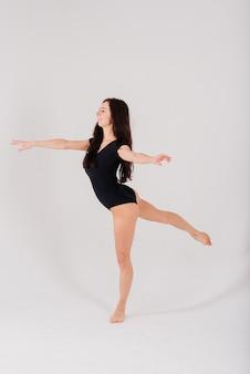 Retrato de uma bailarina dançando em um macacão preto no estúdio em fundo cinza