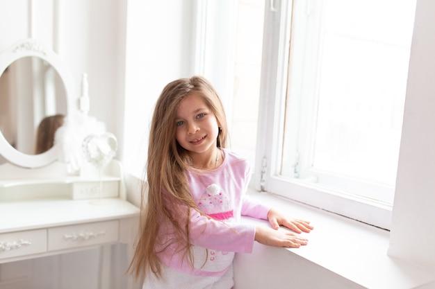 Retrato de uma bela adolescente fica perto da janela branca.