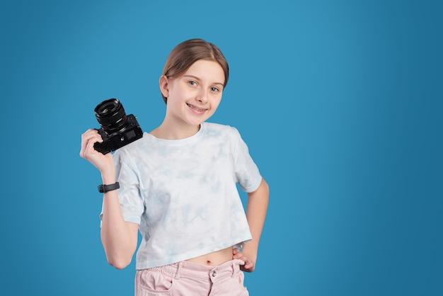 Retrato de uma bela adolescente sorridente posando com uma câmera profissional