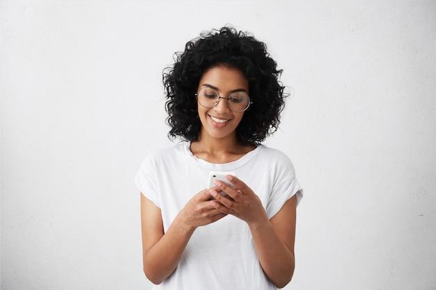 Retrato de uma bela aluna africana vestida casualmente segurando um telefone celular