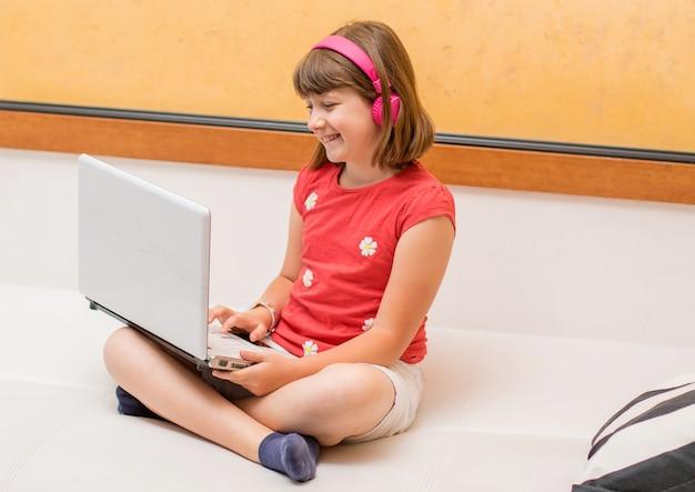 Retrato de uma bela aluna vendo e ouvindo tutoriais em vídeo on-line com fones de ouvido e um pc deitado no sofá em casa