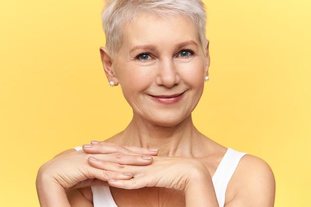 Retrato de uma bela aposentada caucasiana na moda em um top branco, segurando as mãos, olhando para a câmera com um sorriso simpático e fofo, expressando emoções positivas, estando de bom humor