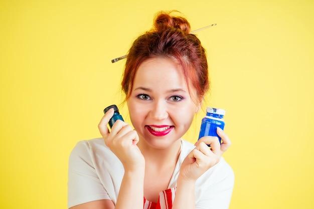 Retrato de uma bela artista de avental segurando uma paleta e um pincel sobre um fundo amarelo no estúdio