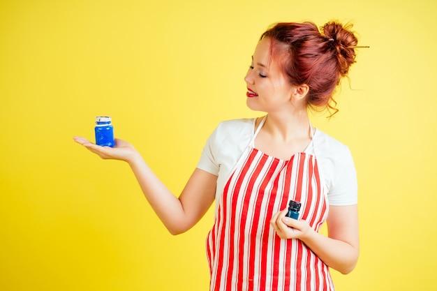 Retrato de uma bela artista em um avental segurando uma paleta e pincel sobre um fundo amarelo no estúdio. inspiração e ideia da musa.
