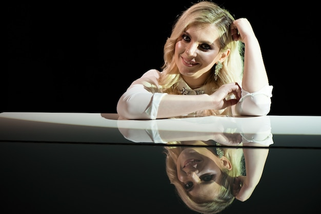 Retrato de uma bela atriz perto de um piano branco.