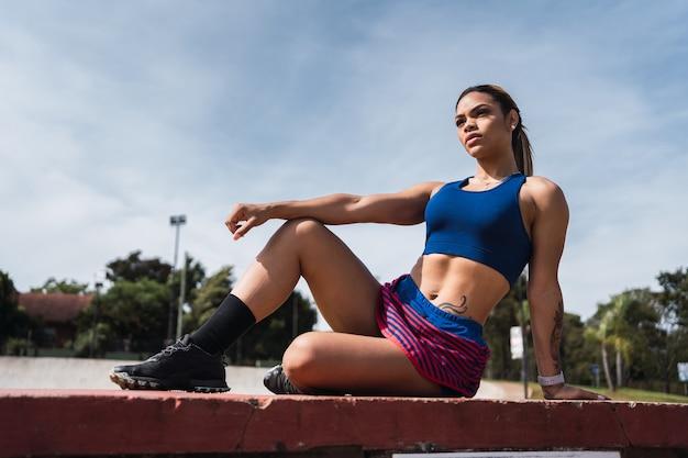 Retrato de uma bela desportista a descansar após sua rotina de exercícios ao ar livre.