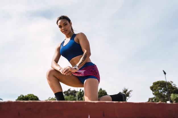 Retrato de uma bela desportista fazendo sua rotina de exercícios ao ar livre.