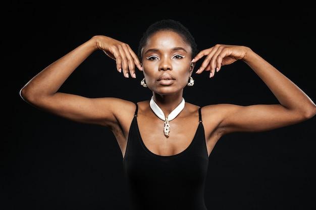 Retrato de uma bela e atraente mulher étnica isolada na parede preta