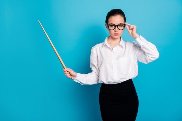 Retrato de uma bela e atraente professora elegante apontando uma vara de madeira isolada sobre um fundo de cor azul brilhante
