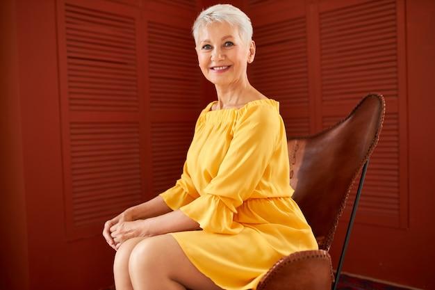 Retrato de uma bela e elegante mulher branca de meia-idade com cabelo loiro curto, sentada confortavelmente em uma poltrona de couro