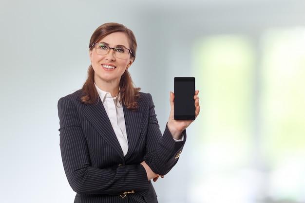 Retrato de uma bela empresária 50 orelhas velhas com telefone celular no escritório.