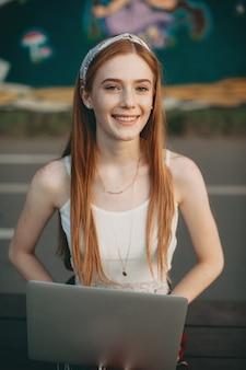 Retrato de uma bela estudante ruiva sentada no parque após a aula com um laptop nas pernas sorrindo.