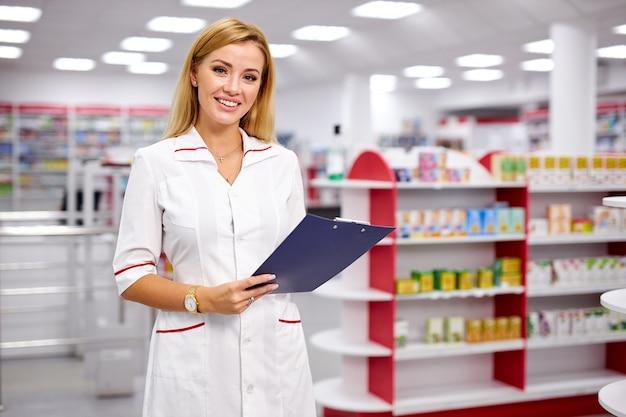 Retrato de uma bela farmacêutica loira bonita escrevendo na área de transferência