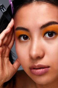 Retrato de uma bela garota asiática, lindo rosto feminino com pele limpa e saudável, close-up de um fundo escuro