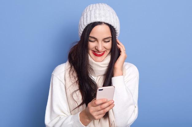 Retrato de uma bela garota atraente e alegre satisfeita segurando nas mãos e usando o telefone celular, lê boas notícias, a senhora fica isolada no espaço azul