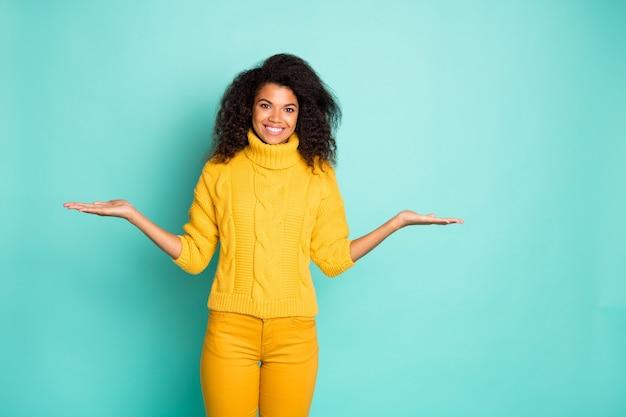 Retrato de uma bela garota atraente na moda alegre de cabelos ondulados em um suéter de tricô segurando dois objetos invisíveis nas palmas das mãos, decidindo isolado sobre a parede de cor azul verde vibrante brilhante brilho vívido