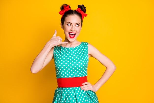 Retrato de uma bela garota encantadora alegre e alegre fingindo ligar para o telefone isolado sobre um fundo de cor amarela vibrante