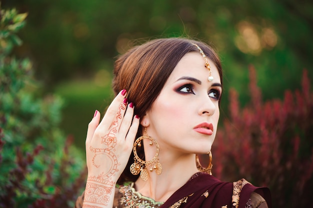 Retrato de uma bela garota indiana. modelo de jovem hindu com tatoo mehndi e jóias kundan. saree de traje tradicional.