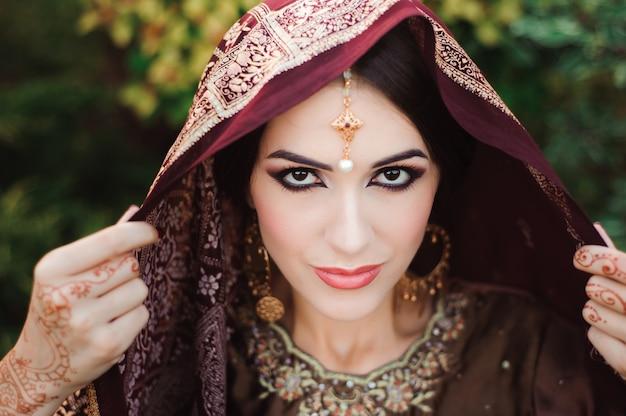 Retrato de uma bela garota indiana. modelo jovem mulher hindu com jóias mehndi e kundan tatoo