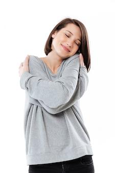 Retrato de uma bela jovem, abraçando-se em pé