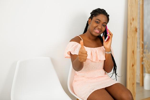 Retrato de uma bela jovem africana em um vestido com um celular e um gesto com a mão