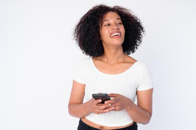 Retrato de uma bela jovem africana feliz pensando enquanto usa o telefone