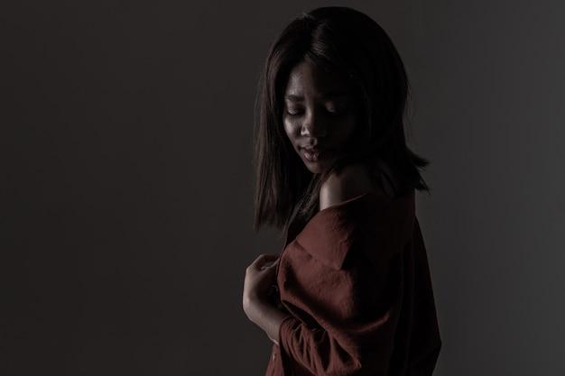 Retrato de uma bela jovem africana natural possing sobre fundo preto