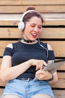 Retrato de uma bela jovem alegre e elegante em fones de ouvido, sentado no parque