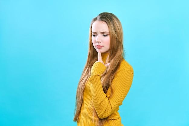 Retrato de uma bela jovem aluna com longos cabelos loiros. em um suéter amarelo.