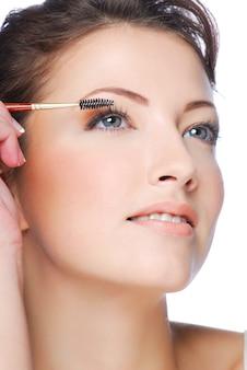 Retrato de uma bela jovem aplicando rímel com um pincel para cílios
