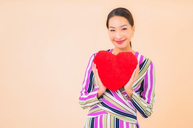 Retrato de uma bela jovem asiática com almofada em forma de coração na cor