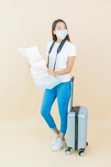 Retrato de uma bela jovem asiática com bagagem e câmera pronta para viajar em fundo bege.