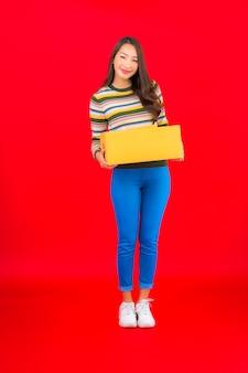 Retrato de uma bela jovem asiática com caixa de pacote na parede vermelha isolada