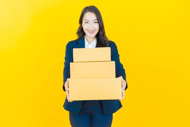 Retrato de uma bela jovem asiática com caixa pronta para envio em amarelo.