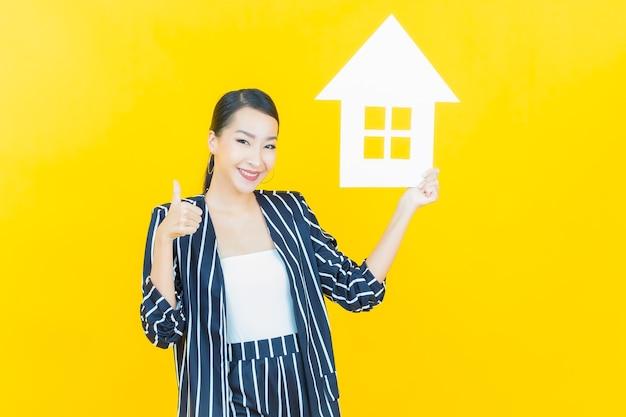 Retrato de uma bela jovem asiática com casa ou sinal de papel em casa na cor de fundo.