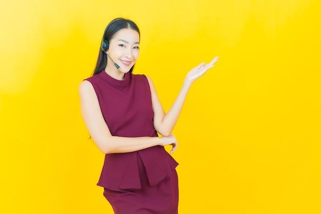 Retrato de uma bela jovem asiática com centro de atendimento ao cliente de call center na parede amarela amarela
