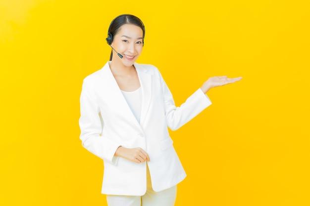 Retrato de uma bela jovem asiática com centro de atendimento ao cliente de call center na parede de cor amarela