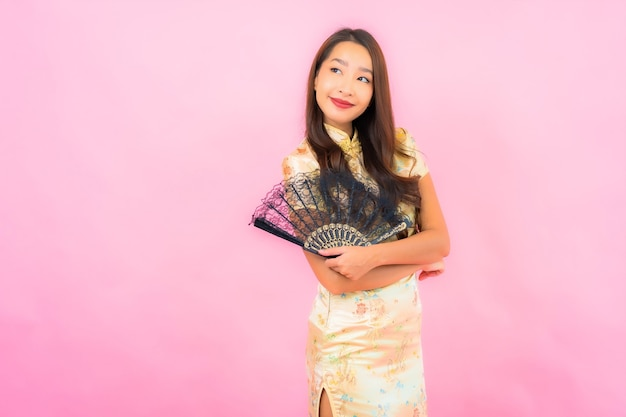 Retrato de uma bela jovem asiática com conceito de ano novo chinês e ventilador na parede colorida