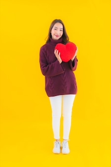 Retrato de uma bela jovem asiática com formato de almofada em forma de coração
