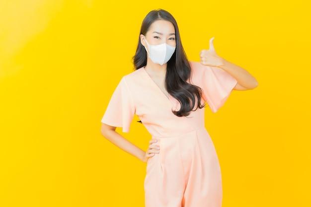 Retrato de uma bela jovem asiática com máscara para proteger o vírus covid19 na parede de cor amarela