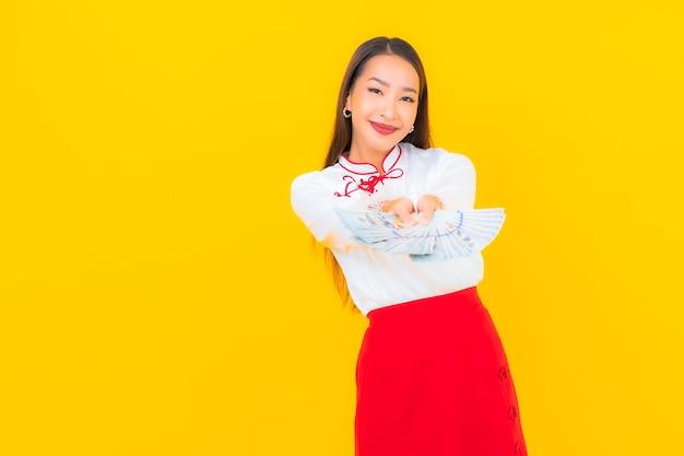 Retrato de uma bela jovem asiática com muito dinheiro e dinheiro em amarelo