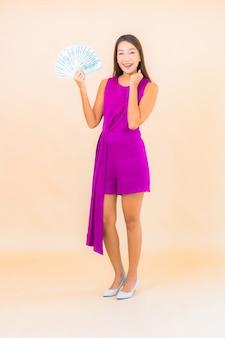Retrato de uma bela jovem asiática com muito dinheiro e dinheiro na cor de fundo.